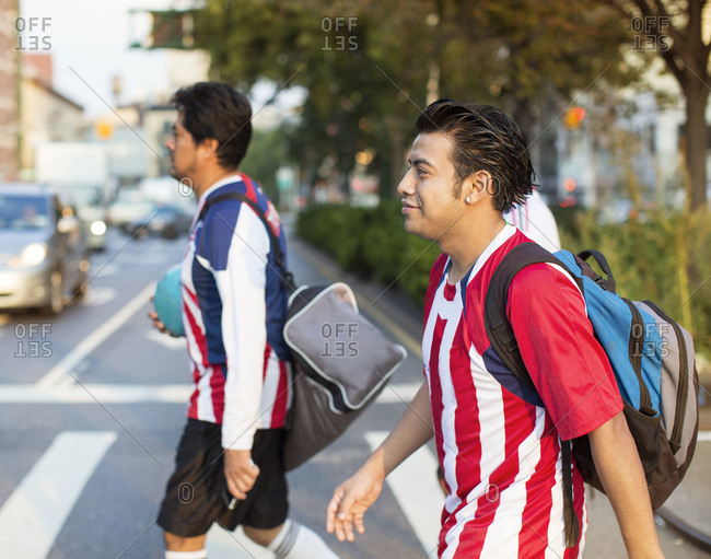 Side view of soccer players crossing the street