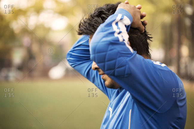 Side view of soccer player standing disappointed