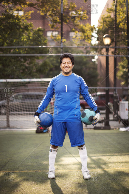 Goalkeeper with two balls on soccer field
