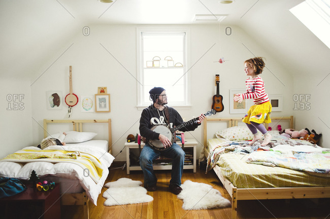 Little girl dancing while father plays the banjo