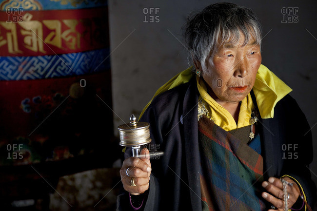 Woman with prayer wheel, Jampey Lhakhang Dzong, Bumthang Valley, Bhutan, October 9, 2011