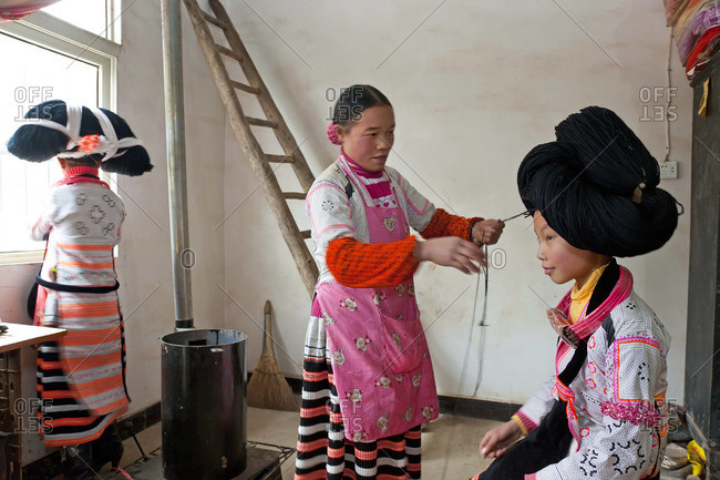 Long Horn Miao woman preparing the headdress of a girl, Sugao, Guizhou Province, China, January 30, 2012