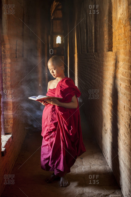 Young monk reading in pagoda, Bagan (Pagan), Myanmar (Burma), February 5, 2013