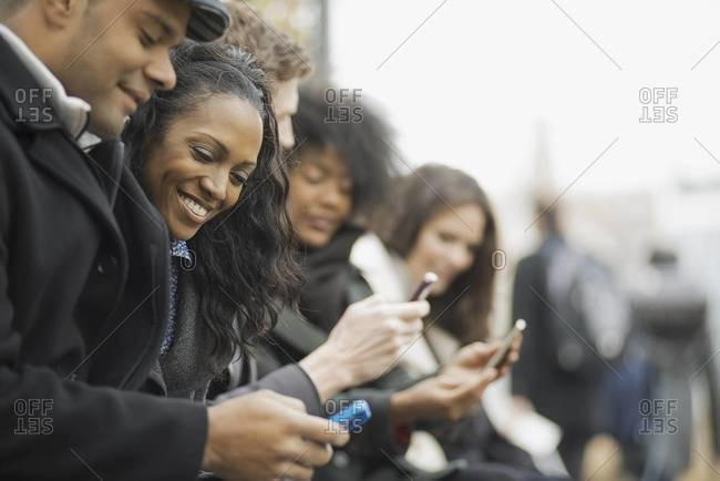 A group of people on the go, keeping in contact, using mobile phones. Men and women standing in a line. Looking up and laughing.