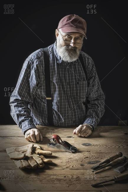 A man working in a reclaimed lumber yard workshop. Holding tools and working on a knotted and uneven piece of wood.