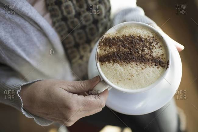 A person holding a full cup of frothy cappuccino coffee in a white china cup.
