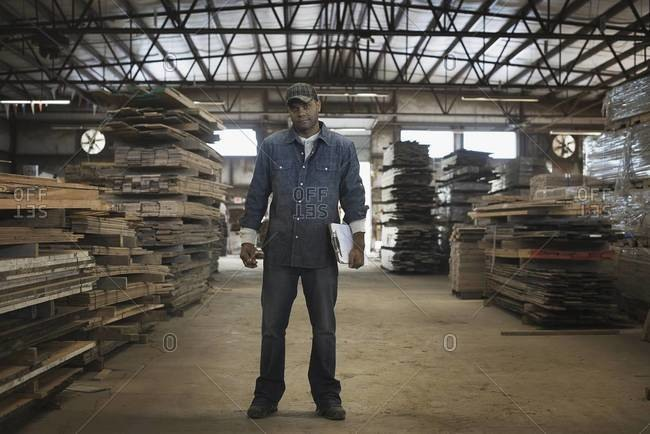 A heap of recycled reclaimed timber planks of wood. Environmentally responsible reclamation in a timber yard. A man in work overalls with a clipboard.