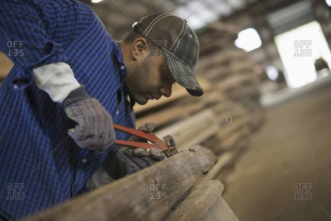 A man working in a reclaimed timber yard