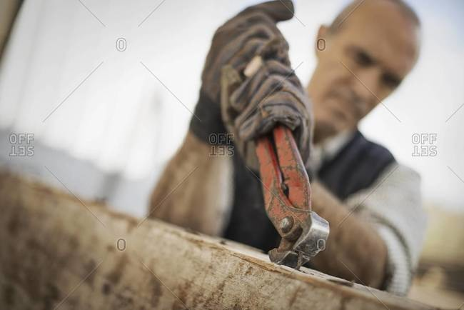 A man working in a reclaimed timber yard.