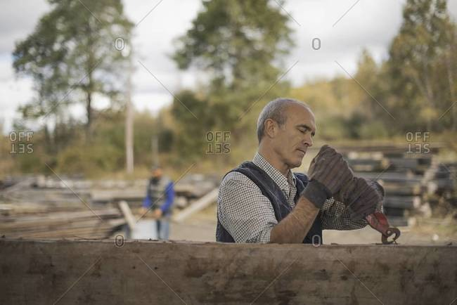 Two men working in a reclaimed timber yard.