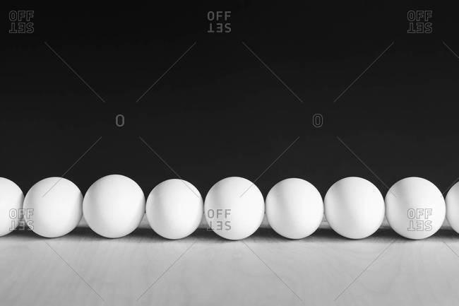 Row of white, free range, eggs, black background