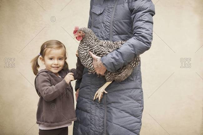 A woman in a grey coat holding a black and white chicken with a red coxcomb under one arm