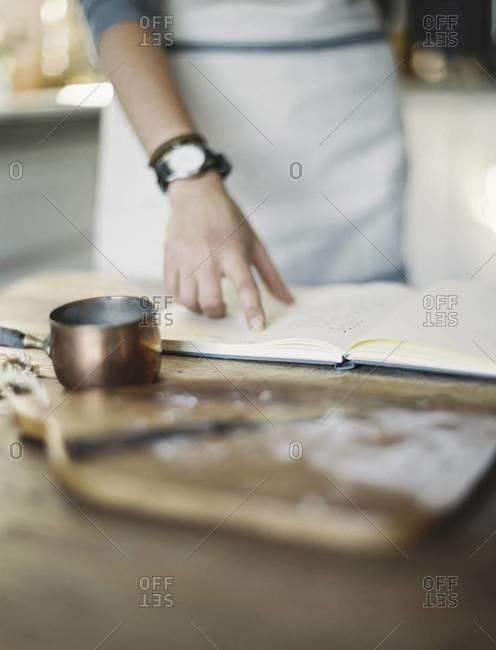 A woman in a domestic kitchen, reading a recipe book.