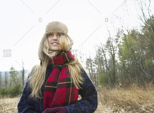 A woman in a warm furry hat and a big red tartan scarf, outdoors in the winter.