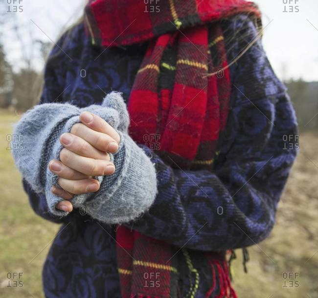 A woman in a tartan scarf and knitted woolen mitts, keeping her hands warm in cold weather.