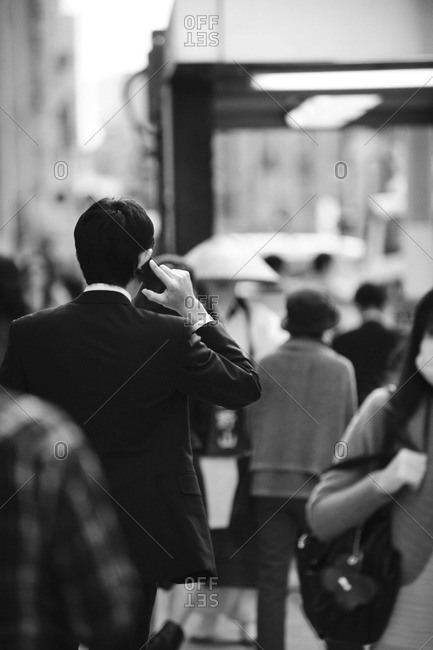 Back view of businessman talking on his cell phone, Ginza district in Tokyo, Japan