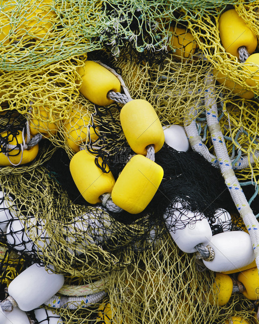 Pile of commercial fishing nets, with yellow and white floats, on the quayside at Fisherman's Terminal, Seattle.