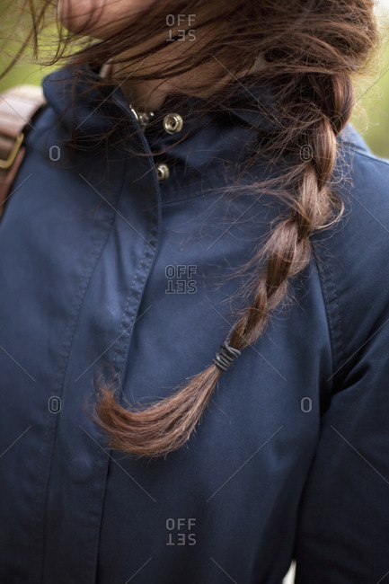 A woman with long brown hair plaited in a braid. Wearing a blue leather jacket. Close up.