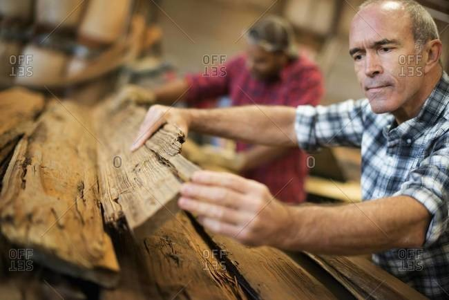 Man measuring and checking planks of wood for re-use and recycling