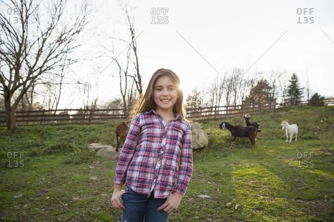 Young girl in the goat paddock enclosure at an animal sanctuary