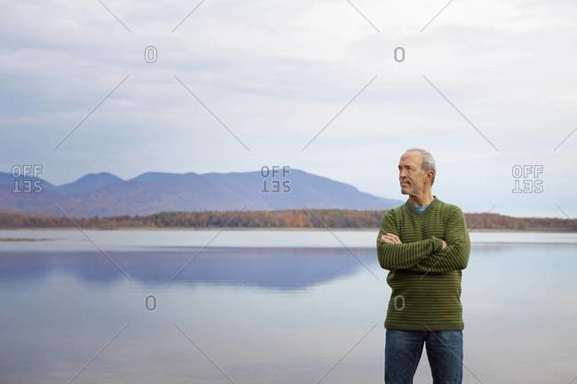 A man with arms folded by the water of a flat calm lake in the mountains