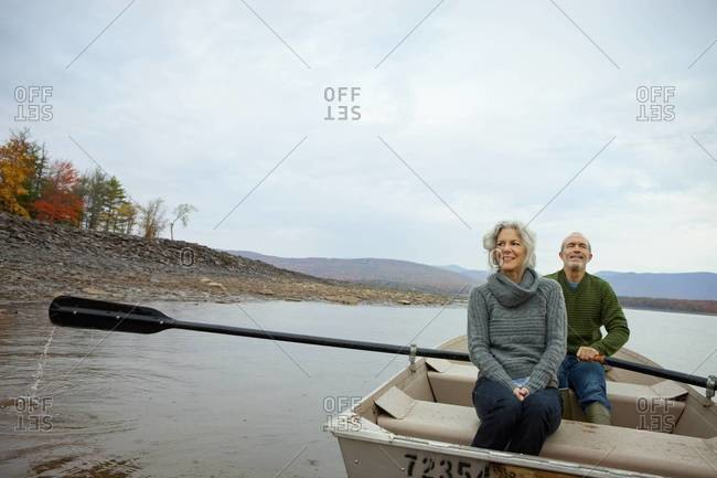 A couple, man and woman sitting in a rowing boat on the water on an autumn day