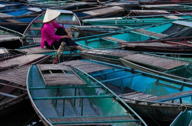 Lost in thought, a woman sits amidst a raft of boats Ninh Binh, Vietnam
