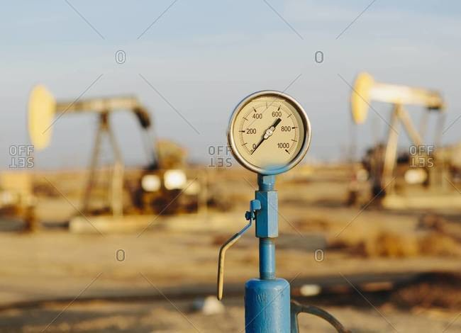 Air pressure gauge with oil rigs in background