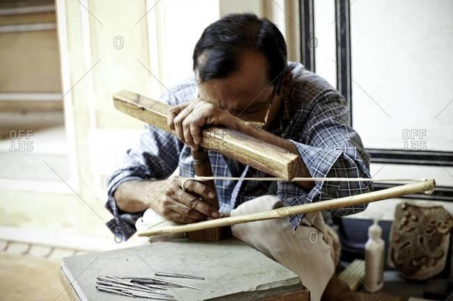 Man carving wood block - Offset