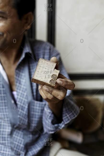 Hand holding wood block - Offset