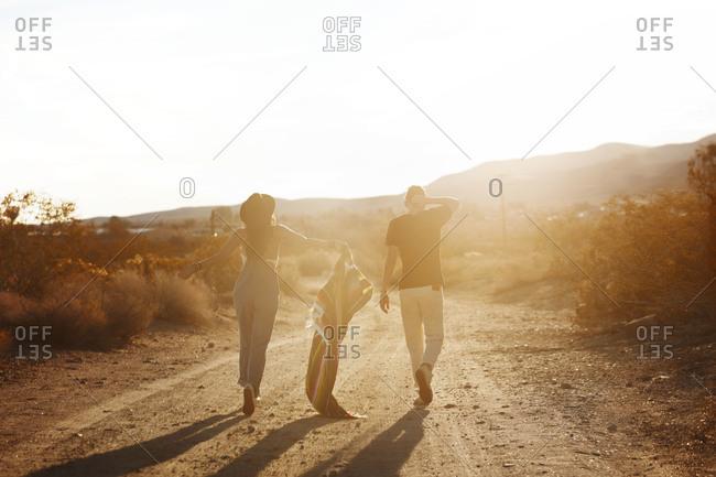Two people walking down dirt road