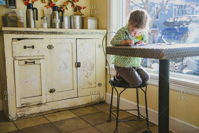 Girl drawing at the table in kitchen