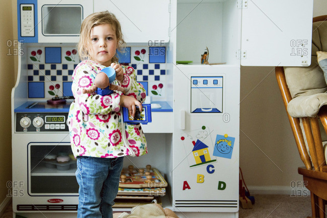 Girl standing in her play kitchen
