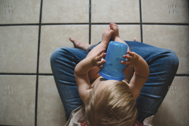 Overhead view of toddler drinking in woman's lap