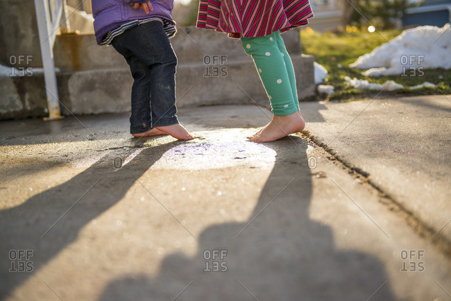Low section view of kids standing barefoot on the sidewalk