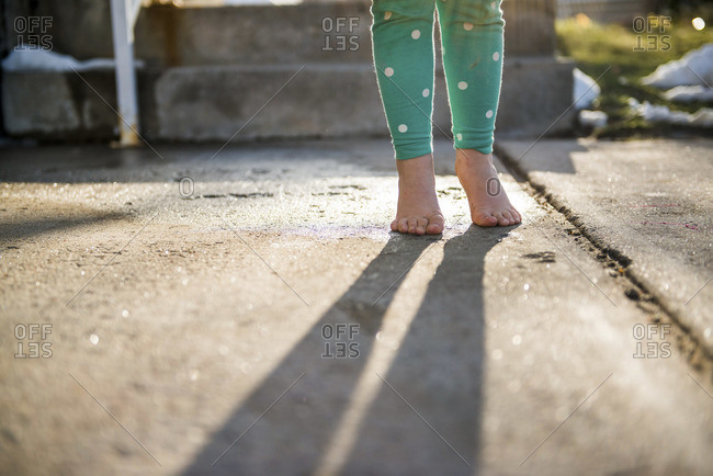 Low section view of a child standing barefoot on the sidewalk