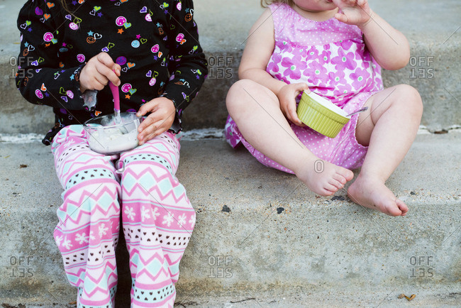 Two girls sitting on the stairs and eating ice cream