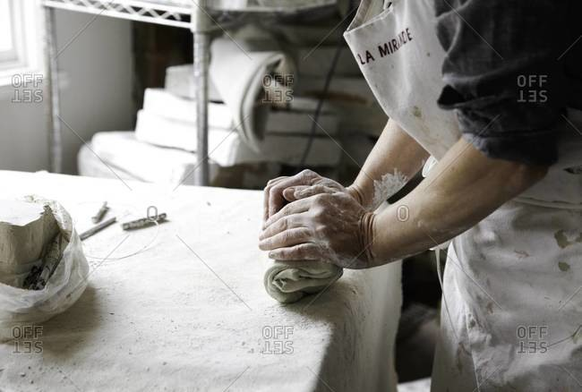 Close up view of artist hand rolling clay