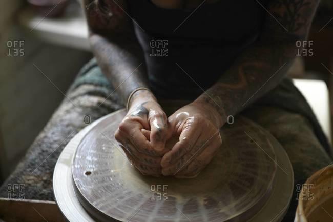 Artist hands on pottery wheel