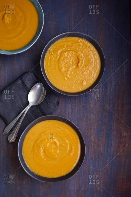 Three bowls of carrot soup with spoons