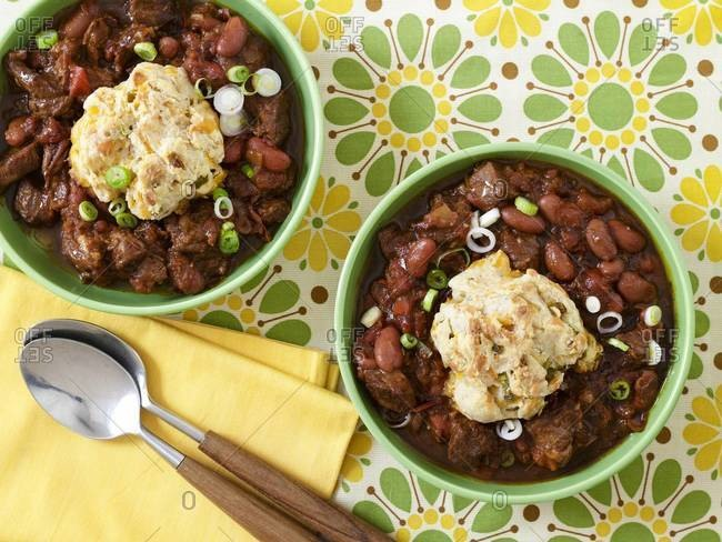 Chili con carne garnished with chopped spring onion, served with cornbread