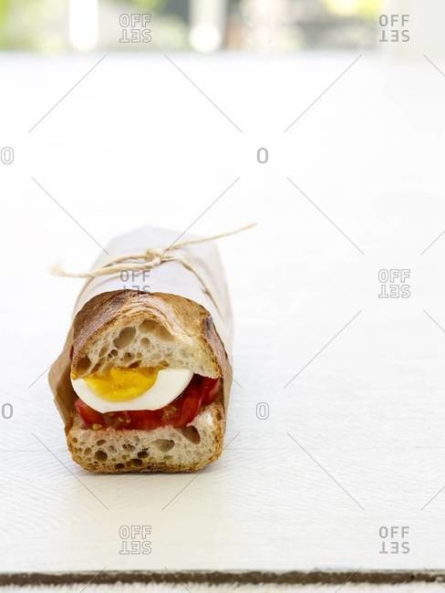 Boiled egg and tomato sandwich in French baguette, wrapped in wax paper