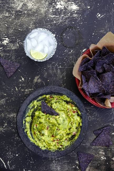 Top view of fresh guacamole, blue chips and margarita cocktail