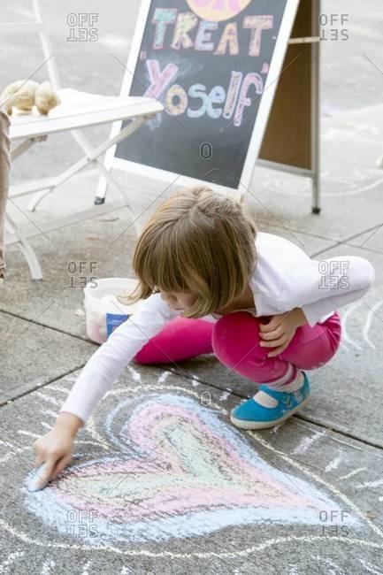 Little girl drawing with chalk on sidewalk