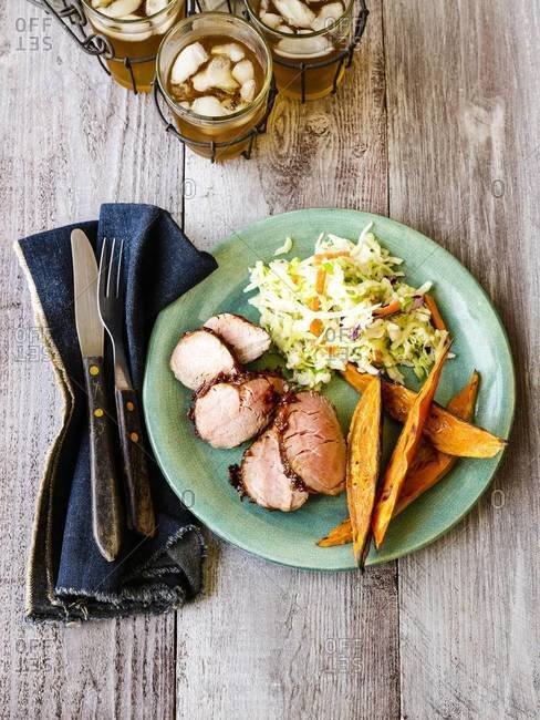 Pork indented with coleslaw and fried sweet potato.