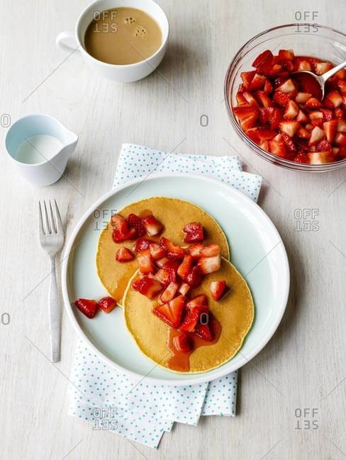 Whole wheat pancakes with fresh strawberries and white coffee