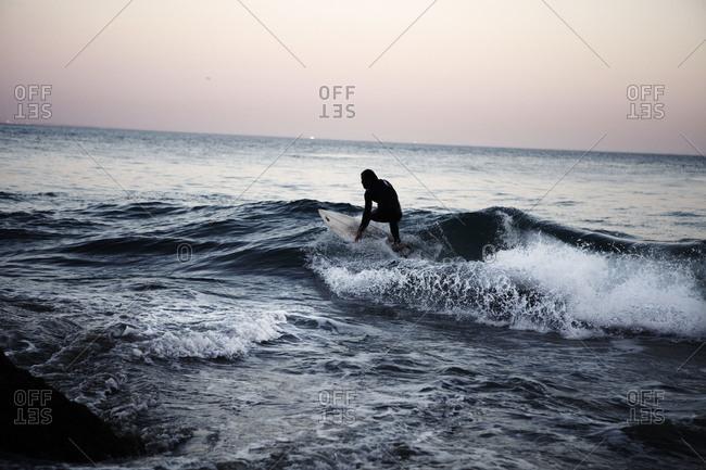 Man surfing at dusk