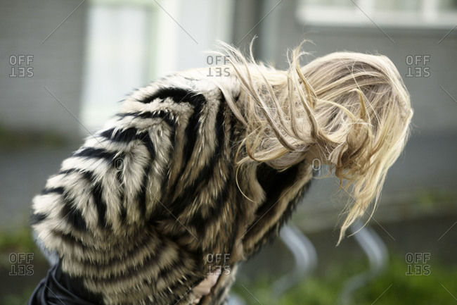 Woman wearing a striped fur coat leaning over