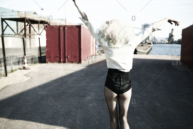 Blonde woman wearing a body suit and white shirt living carefree