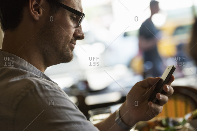 Business on the go. A man sitting at a cafe table, using his mobile phone. Looking down at the screen.